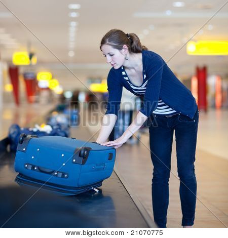 Baggage reclaim at the airport - pretty young woman taking her suitcase off the baggage carousel (color toned image)