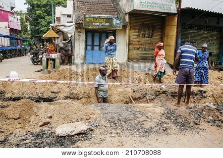 PONDICHERY PUDUCHERY INDIA - SEPTEMBER 04 2017. Unidentified workers with shovels in a trench dig trenches along the road. Concept of hard work in constryuction