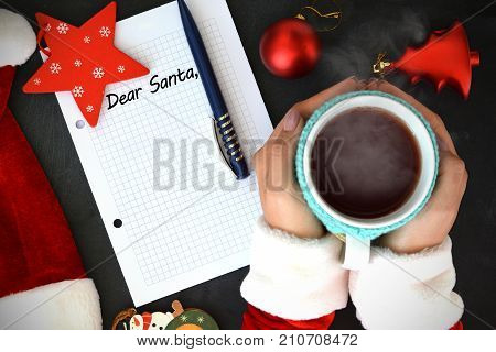 Dear Santa, text on math book with woman hand holding a cup with hot tea near Santa's hat and Christmas accessories - time for Santa's wish list concept