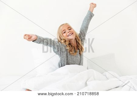 Close-up of beautiful little girl waking up with stretching arms after sleep lying on white bedclothes in her room, looking at camera