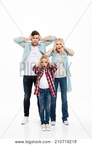 Full length portrait of a unsatisfied upset family standing and covering their ears isolated over white background
