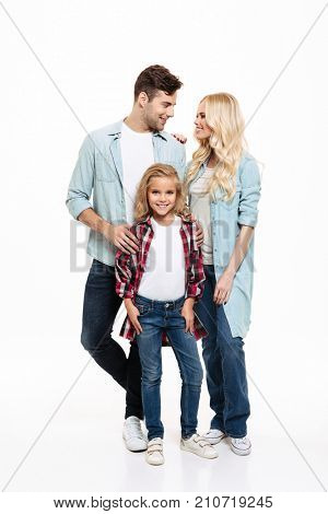 Full length portrait of a young beautiful family standing together isolated over white background