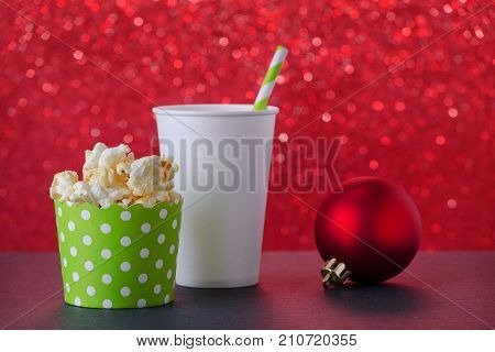 christmas movie with popcorn and drink in paper cup, red background