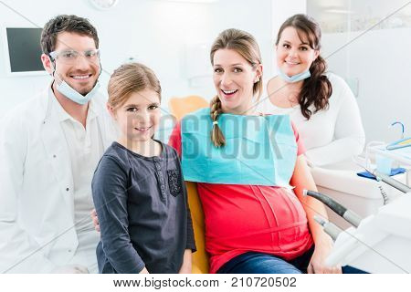 Dentist and his assistant with pregnant woman and child in surgery