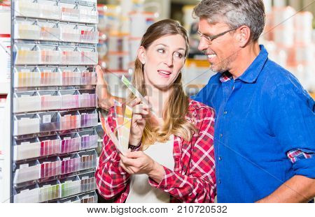 Couple, woman and man, choosing color of wall paint in decoration department of hardware store