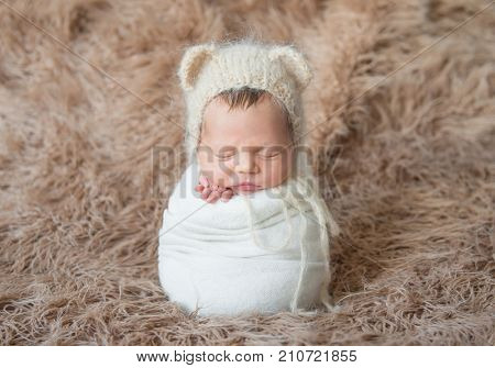 Child wrapped with white blanket, sleeping on furry surface