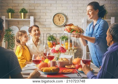 Happy Thanksgiving Day! Autumn feast. Family sitting at the table and celebrating holiday. Grandparents, mother, father and child. Traditional dinner.