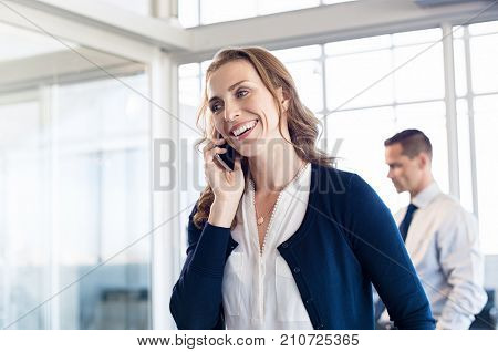 Mature business woman talking over phone in boardroom. Happy businesswoman talking on mobile phone in modern office. Smiling woman having an happy conversation on cellphone at work.