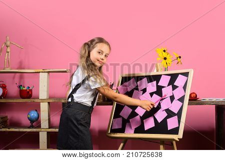 Schoolgirl With Smiling Face In Her Classroom With Bookshelves