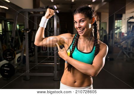 Happy fit girl pointing at her muscles and looking at camera with smile