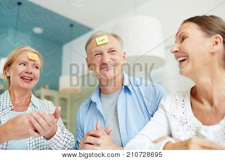 Funny seniors with words written on notepapers stuck on their foreheads playing in group