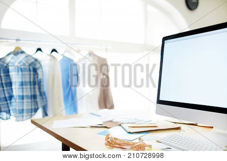 Workplace of fashion designer with computer monitor, measuring-tape, papers and clothes hanging on background
