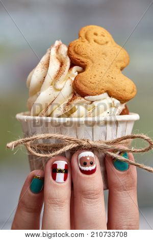 Female hand with festive  Christmas manicure  holding tasty cupcake. Christmas and New Year treat.