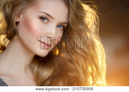 Romantic blonde. Young beautiful cute woman. Beauty girl with long shiny hair, glowing skin and voluminous haircut Sun in the hair. Shining backlight.