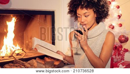 Young woman relaxing with a book and red wine at Christmas sitting in front of a burning fire alongside a decorated tree