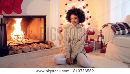 Woman seated by white christmas tree and presents beside fireplace and row of firewood