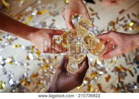 Human hands toasting by flutes with sparkling champagne over floor covered with confetti