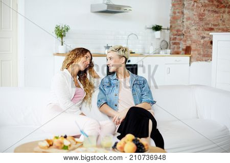 Two happy girls having talk while relaxing on sofa at home