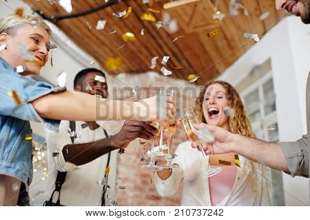 Group of excited friends cheering up with flutes of champagne at party