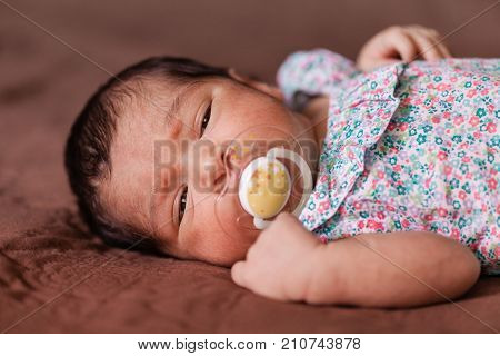 Close up portrait of a cute two weeks old newborn baby girl wearing a floral dress with sleepy eyes
