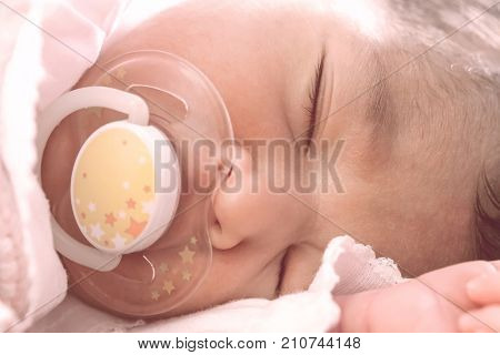 Close up portrait of a cute two weeks old newborn baby girl wearing soft pink knit clothes, sleeping peacefully with a pacifier, aka dummy or soother