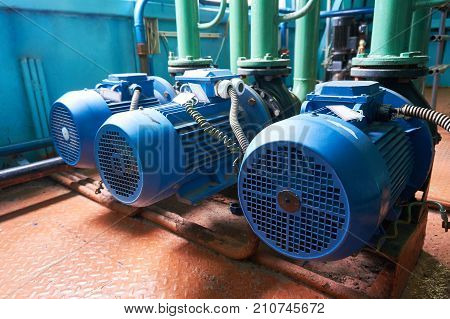 Three blue electric motors with pumps connected to green pipes.