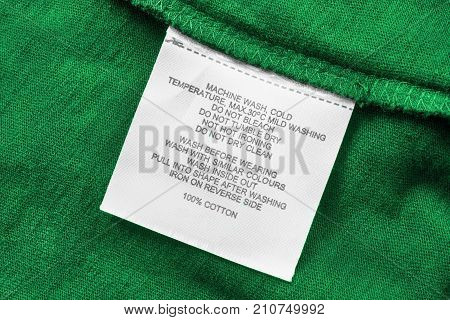 Washing instructions and fabric composition clothes label on green cotton