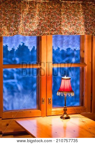 Window view on winter landscape. Snow and cold outside the window, a lamp is burning. Icy pattern on the window. Cozy warm house in eco-style with space for text.