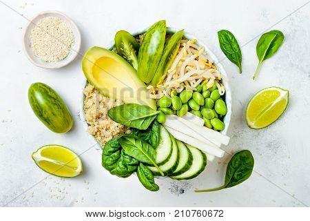 Vegan detox green Buddha bowl recipe with quinoa avocado cucumber spinach tomatoes mung bean sprouts edamame beans daikon radish. Top view flat lay