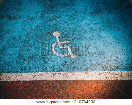 Disabled sign seen on the asphalt with blue marked special parking area