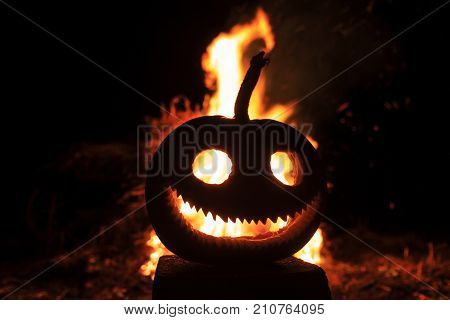 pumpkin head with a terrible smile against the background of fire , Preparation for the holiday, All Saints Day