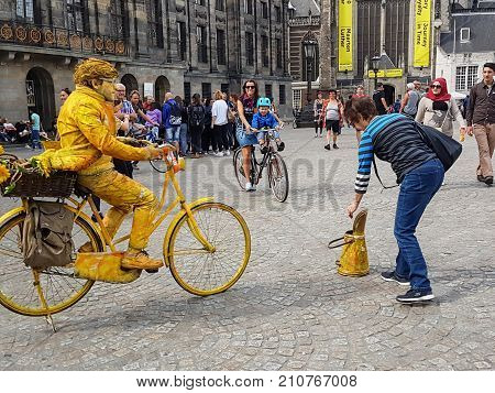 AMSTERDAM HOLLAND - AUGUST 16 2017; people move around Dam Square while tourist places money in street performer yellow man on yellow bike busking container in grainy instagram like image