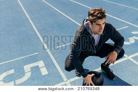 Athlete Sitting On The Running Track With A Medicine Ball