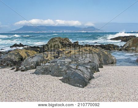 SEASCAPE, WITH A CLOUD COVERED MOUNTAIN,  AND A ROUGH SEA WITH HUGE BOULDERS IN THE FORE GROUND
