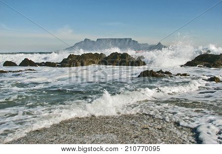 ROUGH WINTER SEA, WITH WAVES BASHING AGAINST SOME BOULDERS AND SPRAYING UP IN TO THE AIR