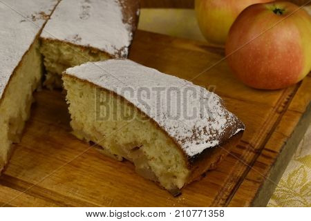 piece of apple pie powdered with sugar powder charlotte on a wooden board with whole apples