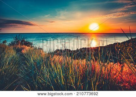 Sunset sky background. Natural Sunset Sunrise Over Ocean. Bright Dramatic Sky And Blue Water. Colorful Nature Landscape. View From The Beach With Green Grass. Bright Filter Toning