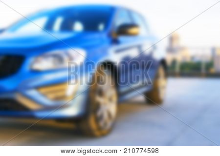 Blurred background of a A modern luxury car on the blur roof of the building. Modern car exterior details