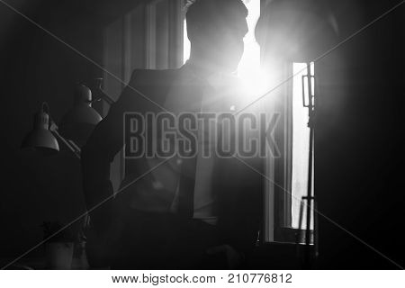 Businessman in a shadowy office with a bright white light flare coming in through a window over his backlit shoulder.