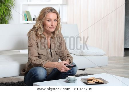 Blond woman sitting on sofa holding remote control