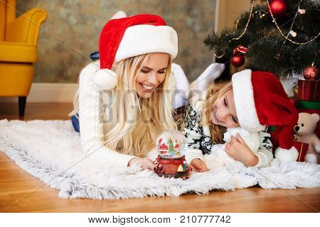 Cheerful woman and little girl in Santa's hat playing with snow ball while lying on white carpet at living room