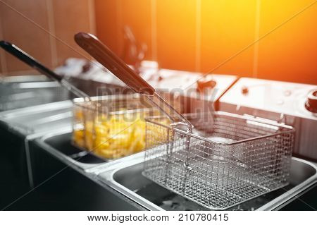 French fries cooking. Grid with strips hop potato lowered into boiling oil. Concept of fast food, delicious food, restaurant
