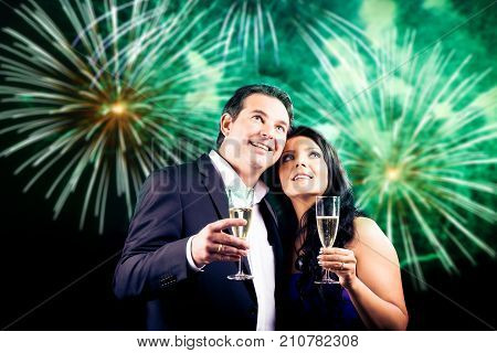 young couple enjoying new year's eve, fireworks in the background. please check my portfolio for a version without the fireworks.