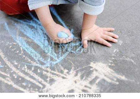 Closeup Photo Of Little Kid Boy Drawing With Colored Chalk On Asphalt