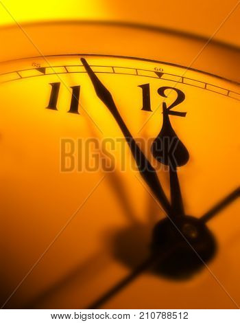 CLOSE UP OF CLOCK FACE WITH HANDS POINTING TOWARDS TWELVE O'CLOCK