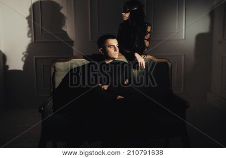beautiful woman in a black dress with a theatrical mask and handsome man , sexual foreplay concept