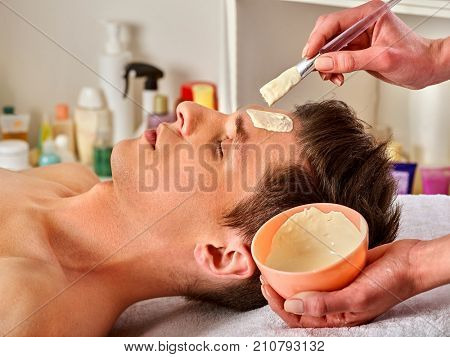 Mud facial mask of man in spa salon. Massage with clay full face. Guy in therapy room. Man lying spa bed. Beautician with bowl therapeutic procedure background. Anti-aging cosmetic mask.