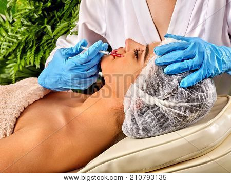 Filler injection for female forehead face. Plastic aesthetic facial surgery in beauty clinic. Cosmetic procedure. Doctor in medical gloves with syringe injects .