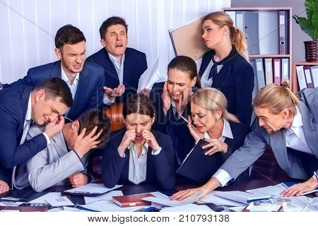 Business people in crisis into office. Team people are unhappy sitting table and working papers. Cabinets with folders and jalousie background. Expenses exceed income for year concept.