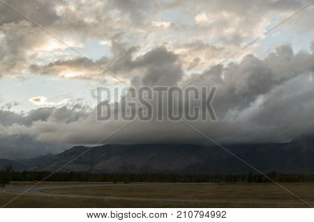Clouds hovering over mountaintops as the sun begins to set in Alberta.
